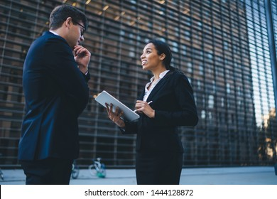 Cheerful ethnic woman using modern tablet with stylus taking notes while talking to elegant businessman standing on street with modern building