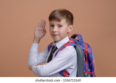 Cheerful European schoolboy with backpack against orange background. He raises his hand and ready to answer question.