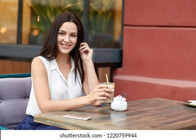 Cheerful European woman enjoys leisure time, drinks milk shake at outdoor cafeteria, spends weekened in big city, waits for call on smart phone, looks positively, dressed in white stylish blouse