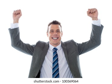 Cheerful excited business executive posing with arms up isolated over white