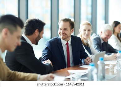 Cheerful excited businessmen in formal suits celebrating success and making handshake while sitting at conference table, they attending management course