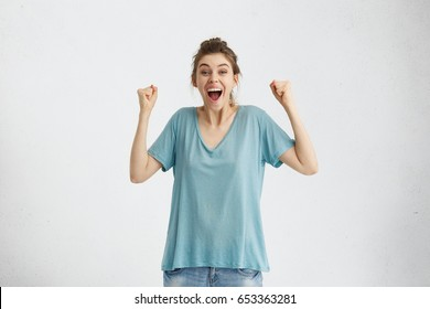 Cheerful excited European female screaming in delight and excitement, clenching fists after being promoted. Happy supportive young mother cheering for her son during football match, isolated on white