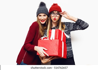 Cheerful excited friends  in sweater holding gift box and looking at camera isolated on  white background. Wearing trendy knitted sweater,  cute hat and  eyeglasses.