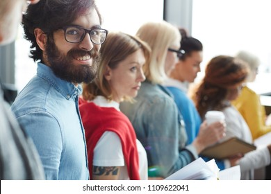 Cheerful excited handsome bearded man in denim shirt wearing eyeglasses standing in line and waiting for his turn while going to report to business forum