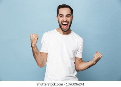 Cheerful excited man wearing blank t-shirt standing isolated over blue background, celebrating success