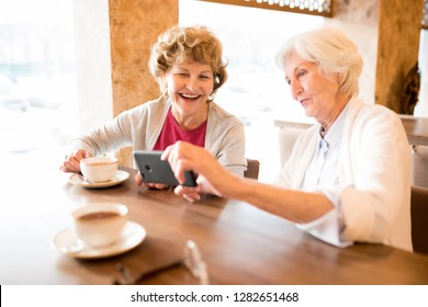 Cheerful excited old ladies sitting at table with coffee cups and laughing while watching video on smartphone