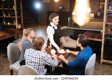 Cheerful excited pretty waitress in apron standing at restaurant table and putting cup on it while bringing tea to client in modern loft establishment