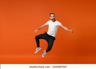 Cheerful excited young man in casual white t-shirt posing isolated on bright orange wall background studio portrait. People lifestyle concept. Mock up copy space. Having fun, fooling around, jumping