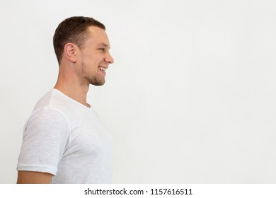 Cheerful excited young man standing against white wall and looking aside. Positive guy in white t-shirt thinking of aspirations. Purposeful man concept