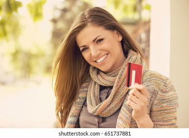 Cheerful excited young woman with credit card standing outdoors on a sunny day