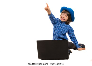 Cheerful executive boy pointing up in front of laptop isolated on white background