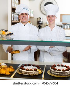 Cheerful experienced man and woman staff offering cakes and buns in bakery