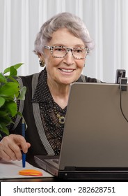 Cheerful experienced teacher looking at web camera on laptop monitor. Smiling old woman is teaching on-line English (or any) language. Vertical portrait.