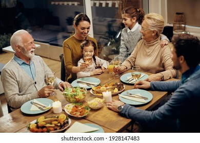 Cheerful extended family communicating while gathering around dining table at home.