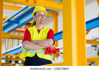Cheerful factory worker smiling with arms crossed