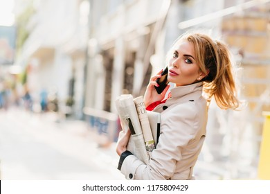 Cheerful fair-haired girl with bright make-up carrying paper and laptop returning home from office. Outdoor portrait of pretty business-lady in beige attire looking around in sunny morning.