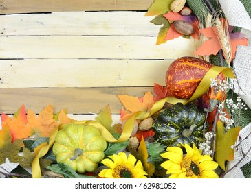 Cheerful fall or autumn border with fall leaves, nuts, sunflowers and squashes with green folded burlap and gold ribbon on a wooden background. Copy space