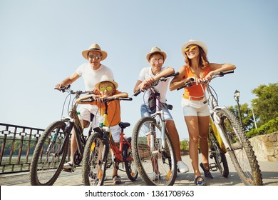 Cheerful family with bicycles standing on embankment