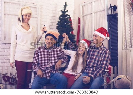 Cheerful family celebrates Christmas together - dad, mom with children teenagers are having fun in front of a Christmas tree on a light background, in anticipation of the holiday.