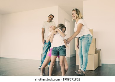 Cheerful family couple and two kids having fun while moving into new apartment. Girls tickling each other and laughing. Full length. Real estate purchase concept