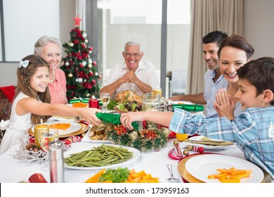 Cheerful family at dining table for christmas dinner in the house