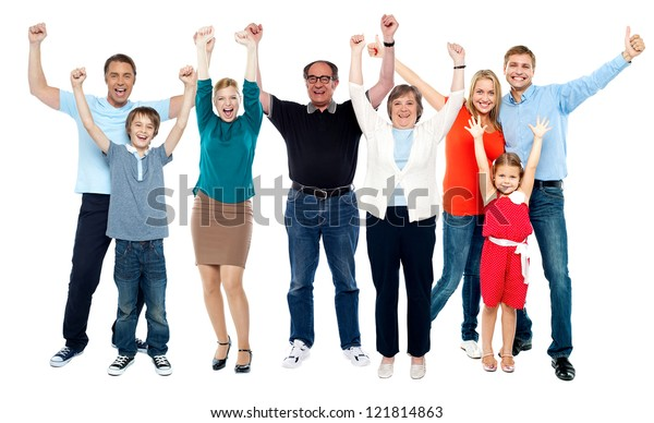 Cheerful family of eight members. Rejoicing together by throwing their hands up in the air in excitement.