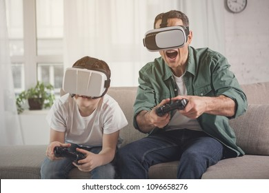 Cheerful family enjoying video game competition. They are holding joysticks and wearing virtual reality googles