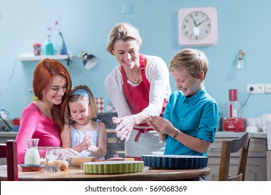 A cheerful family of four having fun while making pastry in a kitchen full of color