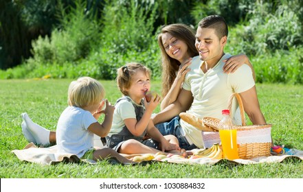 Cheerful family of four on picnic in park at summer day. Focus on girl