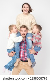 Cheerful family of four on white background. Father holds children and wife in his arms.