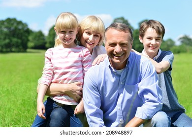 Cheerful family of four posing together, outdoors.