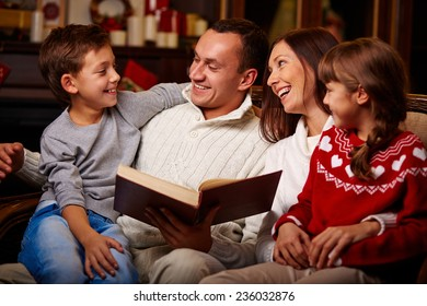 Cheerful family of four reading together at home