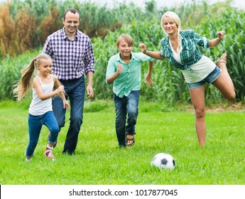 Cheerful  family of four with teenager and little girl playing football on field
