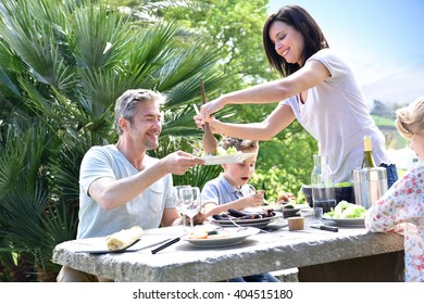 Cheerful family having outdoor lunch