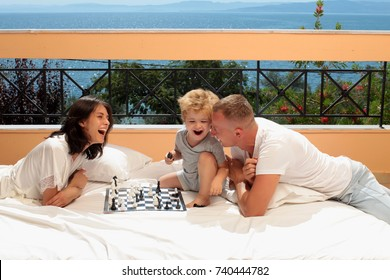 Cheerful family at home, Daddy and his young daughter lying on the wooden floor are playing with a wooden game. Happy family. Lifestyle, travel, vacation, tourism, dream. Childhood. Home concept.