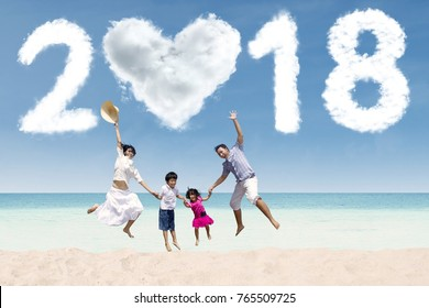 Cheerful family jumping together under clouds shaped numbers 2018 and heart. Shot in the beach