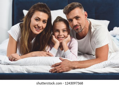 cheerful family laying in bed together