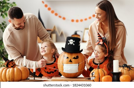 Cheerful family   makes jack o lantern  in medical masks out of a pumpkin and  decorates house  in cozy kitchen during Halloween celebration at home during the covid19 coronavirus pandemic