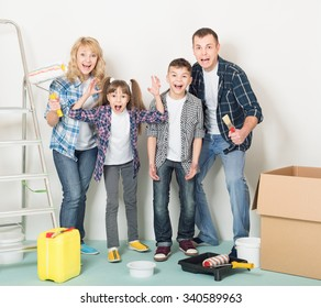 Cheerful family makes repairs at home. Happy mother, father, son and daughter - painting wall at room