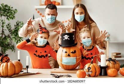 Cheerful family  in medical masks  makes jack o lantern   out of a pumpkin and  scare for camera  in cozy kitchen during Halloween celebration at home during the covid19 coronavirus pandemic