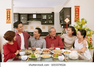 Cheerful family members talking at Chinese New Year celebration dinner. Scrolls wishing luck and wealth in the background