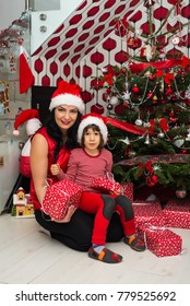 Cheerful family of mother and son posing together in front of Christmas tree in their home