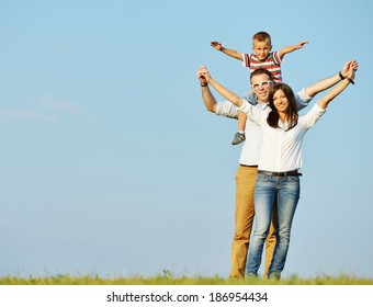 Cheerful family on beautiful summer meadow with sky in background