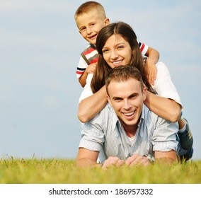 Cheerful family on beautiful summer meadow enjoying and having fun