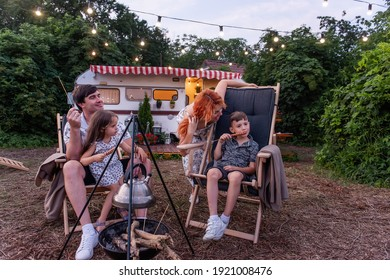 Cheerful family on picnic outside the city, sausages on skewers are fried over fire. Sitting on wooden deck chairs by the trailer track. Parents fool around with children. Happy vacation, weekend trip