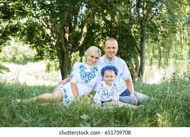 Cheerful family in a park, Dad, mom and their lovely daughter are on the grass while they are looking at camera