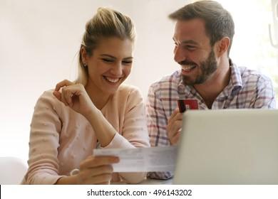 Cheerful family paying bills at home.  E-banking.