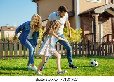 Cheerful family playing football on the backyard lawn
