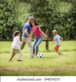 Cheerful family playing football in a park