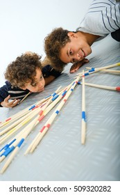 Cheerful family playing giant mikado in the living room at home